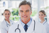Charismatic doctor standing with colleagues — Stock Photo