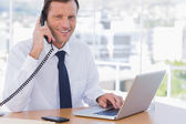 Smiling businessman posing while he is on the phone — Stock Photo