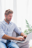 Serious man using his laptop on a couch — Stock Photo