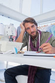 Attractive fashion designer working at his desk — Stock Photo