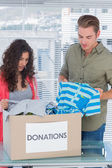 Serious volunteers taking out clothes from a donation box — Stock Photo