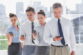 Serious business standing together in line with their mobile — Stock Photo