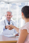 Cheerful doctor shaking hands to patient — Stock Photo