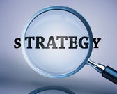 Magnifying glass showing strategy word — Stock Photo