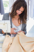 Fashion designer cutting textile — Stock Photo