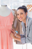 Attractive fashion designer adjusting dress — Stock Photo