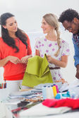 Three fashion designers holding textile — Stock Photo