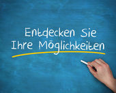 Man writing entdecken sie ihre moglichkeiten with a chalk — Stock Photo
