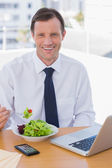 Cheerful businessman eating a salad on his desk — Stock Photo