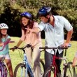 Parents showing the direction to children while they are riding bicycle — Video