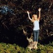 Cheerful blonde little girl jumping on a trampoline — Stock Video #27021349
