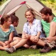 Family sitting in front of their tent spending time together — Stock Video #27022387