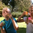 Cheerful siblings having fun with bubbles — Stock Video