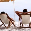 Couple relaxing under parasol — Vídeo de stock