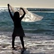 Stock Video: Silhouette of womholding her sarong in air