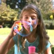 Cute young girl blowing into a bubble wand — Stock Video