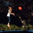 Cheerful siblings having fun with a basketball on a trampoline — Stock Video #27025561