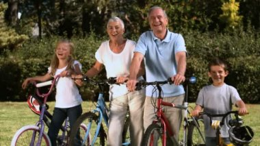 Multi-generation family standing in a park with their bicycles — Stock Video