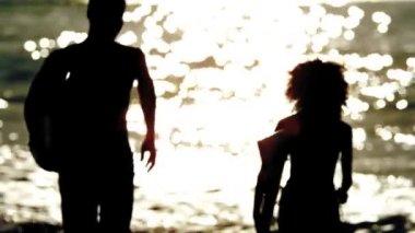 Silhuetas de amigos segurando a prancha e correndo na praia — Vídeo Stock