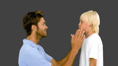 Hombre presionando las mejillas infladas de su hijo sobre fondo gris — Vídeo de stock