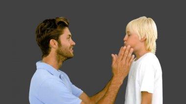 Homem pressionando as bochechas infladas de seu filho no fundo cinza — Vídeo Stock