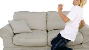 Boy jumping on the sofa on white background — Stock Video