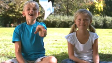 Brother throwing a paper airplane next to his sister — Stock Video