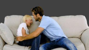 Ojciec łaskotanie syna na kanapie na szarym tle — Wideo stockowe