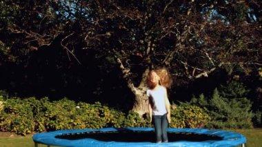 Little girl having fun on a trampoline — Stock Video
