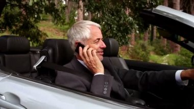 Happy businessman phoning in his convertible car — Stock Video
