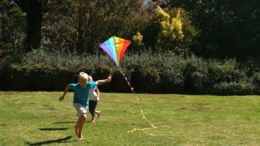 Little girl running after her brother playing with a kite — Stock Video