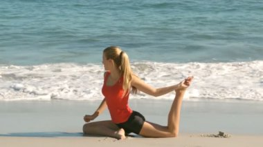 Woman stretching her leg on the beach — Vídeo de Stock