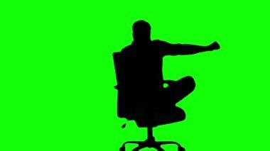 Silhuett av man vrida av snurrstol på grön skärm — Stockvideo