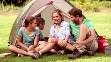 Family sitting in front of their tent spending time together — Stock Video