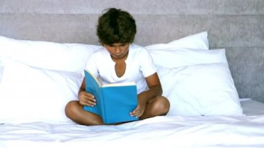 Child reading a book in bedroom — Stock Video
