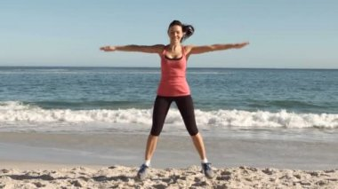 Happy attractive woman working out on the beach — Stock Video