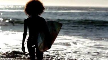 Silhueta de uma mulher correndo na praia com sua prancha de surf — Vídeo Stock