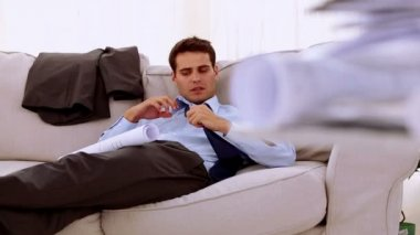 Businessman lying on couch and looking at a document — Stock Video