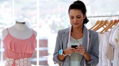 Pretty fashion designer texting in her studio — Stock Video