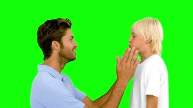 Man pressing inflated cheeks of his son on green screen — Stok video