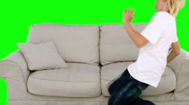 Boy jumping on the sofa on green screen — Stock Video