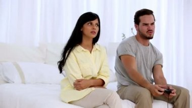 Upset woman sitting next to her boyfriend playing at video game — Stock Video