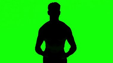 Silhouette of a man tensing muscles on green screen — Stock Video