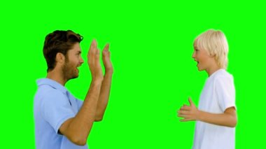 Man giving high five to his son on green screen — Stock Video