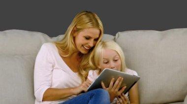 Mãe e filha usando tablet digital no sofá em câmera lenta — Vídeo stock