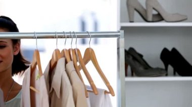 Beautiful woman picking clothes on a clothes rail — Stok video