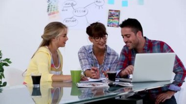 Attractive designers working together with a laptop — Stock Video