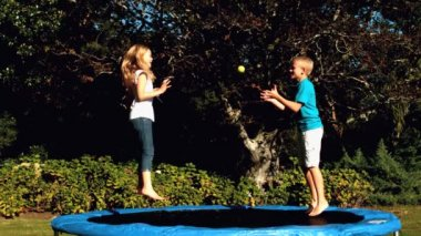 Cheerful siblings having fun with a ball on a trampoline — Stock Video