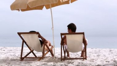 Couple under parasol spending time together — Stock Video