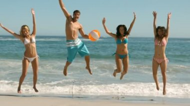Amigos felices saltando y jugando en la playa — Vídeo de Stock